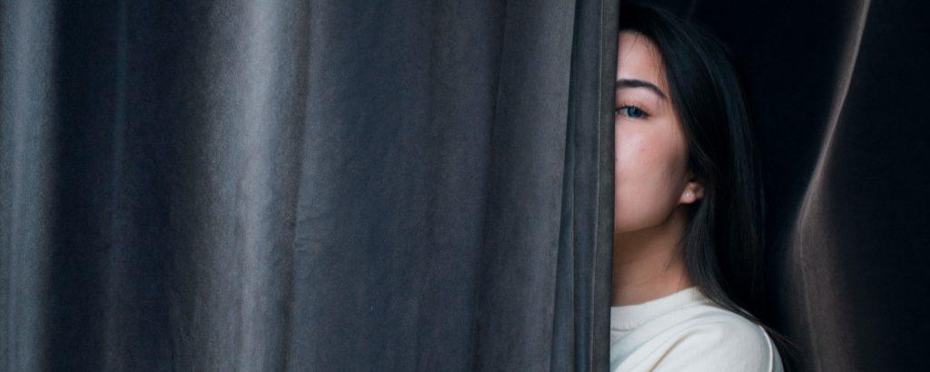 Angst-aufzufliegen-Frau-hinter-Vorhang
